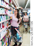 Купить «Positive young woman standing with shopping cart», фото № 29587135, снято 24 января 2019 г. (c) Яков Филимонов / Фотобанк Лори