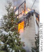 Ель с новогодними шарами на фоне горящего дачного дома. Стоковое фото, фотограф Сайганов Александр / Фотобанк Лори