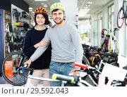 Portrait of adult couple in helmet standing with bicycle in the store. Стоковое фото, фотограф Яков Филимонов / Фотобанк Лори