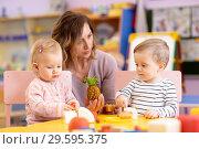Купить «Preschool teacher with babies playing with colorful toys at kindergarten», фото № 29595375, снято 5 июля 2020 г. (c) Оксана Кузьмина / Фотобанк Лори