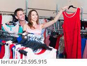 Купить «Man and woman discussing the purchase of dress», фото № 29595915, снято 11 апреля 2017 г. (c) Яков Филимонов / Фотобанк Лори