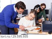 Купить «teacher helping female student preparing for exam in computer class», фото № 29595935, снято 14 ноября 2018 г. (c) Яков Филимонов / Фотобанк Лори