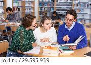 Купить «Tutor helping girls in library», фото № 29595939, снято 14 ноября 2018 г. (c) Яков Филимонов / Фотобанк Лори