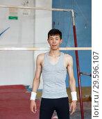 Купить «Man posing in acrobatic hall», фото № 29596107, снято 18 июля 2018 г. (c) Яков Филимонов / Фотобанк Лори
