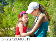 Купить «Little girl four years old with sad face expression sitting on the legs of a woman, with caps, in the forest of the countryside.», фото № 29603519, снято 17 июня 2018 г. (c) easy Fotostock / Фотобанк Лори