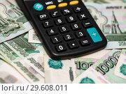 Купить «Калькулятор лежит на тысячных банкнотах», эксклюзивное фото № 29608011, снято 19 декабря 2018 г. (c) Игорь Низов / Фотобанк Лори