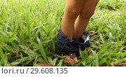 Crop kid with pants down on grass. Стоковое видео, видеограф Ekaterina Demidova / Фотобанк Лори