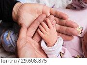 Маленькая рука новорожденного лежит на руках отца и матери, крупный план. Стоковое фото, фотограф Кекяляйнен Андрей / Фотобанк Лори