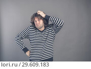 Купить «Puzzled guy with messy hair, frowning and looking unsatisfied scratching head, thinking deeply about something on grey wall background. Human facial expression, emotion, feeling, sign body language», фото № 29609183, снято 1 декабря 2018 г. (c) Marina Sharova / Фотобанк Лори