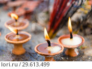 Terra-cota oil lamps as religious offerings at temple in Nepal. Incence sticks over blurred background. Стоковое фото, фотограф Constantin Stanciu / easy Fotostock / Фотобанк Лори