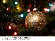 Купить «Новогодний шарик висит на ёлке на фоне огоньков», эксклюзивное фото № 29616903, снято 25 декабря 2018 г. (c) Игорь Низов / Фотобанк Лори