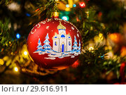 Купить «Новогодний шарик с изображением храма висит на ёлке», эксклюзивное фото № 29616911, снято 25 декабря 2018 г. (c) Игорь Низов / Фотобанк Лори