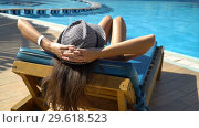 Купить «Pretty woman relaxing in a lounger near of the swimming pool. Concept of the travel vocation», видеоролик № 29618523, снято 24 декабря 2018 г. (c) Happy Letters / Фотобанк Лори