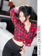 Купить «Cheerful young woman posing near a white sofa.», фото № 29619999, снято 8 января 2016 г. (c) Сергей Сухоруков / Фотобанк Лори