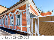 Old wooden house with carved platbands on city street (2018 год). Редакционное фото, фотограф FotograFF / Фотобанк Лори