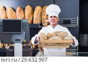 Купить «Smiling male baker is showing tasty bread», фото № 29632907, снято 22 апреля 2017 г. (c) Яков Филимонов / Фотобанк Лори
