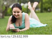 Купить «young girl using digital tablet while lying in green spring garden», фото № 29632999, снято 18 апреля 2017 г. (c) Яков Филимонов / Фотобанк Лори