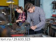 Купить «Master is standing near vise equipment», фото № 29633323, снято 10 октября 2017 г. (c) Яков Филимонов / Фотобанк Лори