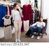 Купить «Family choosing dress and blouse at clothing shop», фото № 29633347, снято 24 октября 2016 г. (c) Яков Филимонов / Фотобанк Лори