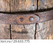 Купить «Фрагмент склепанного металлического обруча на старой деревянной бочке», фото № 29633775, снято 8 августа 2018 г. (c) Вячеслав Палес / Фотобанк Лори