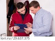 Купить «Young courier is delivering order for adult man», фото № 29637375, снято 5 февраля 2018 г. (c) Яков Филимонов / Фотобанк Лори