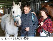 Купить «Portrait of couple standing at stable», фото № 29637459, снято 26 ноября 2018 г. (c) Яков Филимонов / Фотобанк Лори
