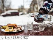 Купить «Мужчина разливает водку в рюмки зимой на улице», эксклюзивное фото № 29640827, снято 1 января 2019 г. (c) Игорь Низов / Фотобанк Лори
