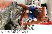 Купить «Portrait of muscular guy lifting dumbbells at gym», видеоролик № 29641035, снято 15 ноября 2018 г. (c) Яков Филимонов / Фотобанк Лори