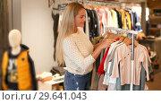 Купить «Young blonde woman choosing baby clothes small size in shop», видеоролик № 29641043, снято 13 ноября 2018 г. (c) Яков Филимонов / Фотобанк Лори