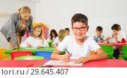 Купить «Diligent schoolboy drawing at lesson», фото № 29645407, снято 15 ноября 2018 г. (c) Яков Филимонов / Фотобанк Лори