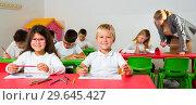 Купить «Female teacher helping schoolkids drawing with color pencils in classroom», фото № 29645427, снято 22 января 2019 г. (c) Яков Филимонов / Фотобанк Лори