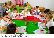 Купить «Female teacher helping schoolkids drawing with color pencils in classroom», фото № 29645431, снято 22 января 2019 г. (c) Яков Филимонов / Фотобанк Лори