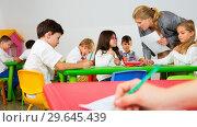 Купить «Female teacher helping schoolkids drawing with color pencils in classroom», фото № 29645439, снято 15 ноября 2018 г. (c) Яков Филимонов / Фотобанк Лори