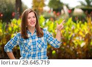 Купить «Smiling girl shows thumbs up on something useful», фото № 29645719, снято 10 ноября 2017 г. (c) Pavel Biryukov / Фотобанк Лори