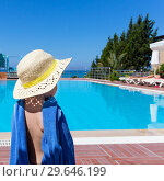 Купить «Little girl with blue towel and straw hat stands with her back and looks at the pool», фото № 29646199, снято 18 июля 2019 г. (c) Светлана Кузнецова / Фотобанк Лори