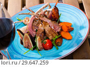 Купить «Fried lamb ribs served with garnish of vegetables and fresh figs», фото № 29647259, снято 21 сентября 2019 г. (c) Яков Филимонов / Фотобанк Лори