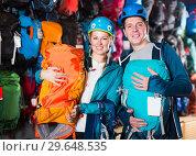 Купить «couple of travelers at sports store, selects backpacks for camping», фото № 29648535, снято 25 октября 2017 г. (c) Яков Филимонов / Фотобанк Лори