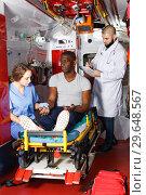Купить «Emergency doctors providing first aid to man in ambulance auto», фото № 29648567, снято 30 ноября 2018 г. (c) Яков Филимонов / Фотобанк Лори