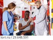 Купить «Paramedic team providing first aid to man», фото № 29648591, снято 30 ноября 2018 г. (c) Яков Филимонов / Фотобанк Лори