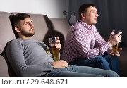 Купить «Indifferent gu with friend emotionally watching tv», фото № 29648671, снято 7 февраля 2018 г. (c) Яков Филимонов / Фотобанк Лори