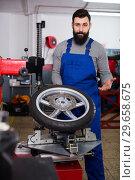 Купить «Worker repairing wheel», фото № 29658675, снято 19 апреля 2019 г. (c) Яков Филимонов / Фотобанк Лори