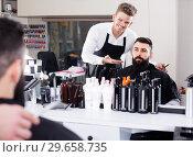 Купить «smiling guy stylist demonstrating final haircut to client at hairdressing salon», фото № 29658735, снято 27 января 2017 г. (c) Яков Филимонов / Фотобанк Лори