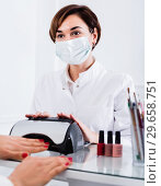 Купить «Female client doing nails in shellac technique», фото № 29658751, снято 2 февраля 2017 г. (c) Яков Филимонов / Фотобанк Лори