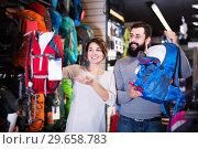 Купить «Couple choosing rucksack in store», фото № 29658783, снято 24 февраля 2017 г. (c) Яков Филимонов / Фотобанк Лори