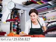 Купить «Seller measuring cloth», фото № 29658827, снято 4 января 2017 г. (c) Яков Филимонов / Фотобанк Лори