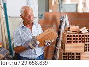 Купить «Man working with red brick», фото № 29658839, снято 19 июня 2018 г. (c) Яков Филимонов / Фотобанк Лори