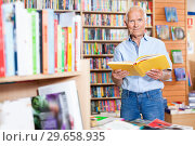 Купить «Focused elderly man looking for information in books in bookstore», фото № 29658935, снято 11 июня 2018 г. (c) Яков Филимонов / Фотобанк Лори