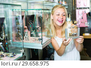 Купить «girl choosing earrings in bijouterie boutique», фото № 29658975, снято 23 марта 2019 г. (c) Яков Филимонов / Фотобанк Лори