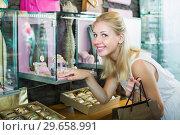 Купить «Smiling young woman customer looking fashion jewellery», фото № 29658991, снято 23 марта 2019 г. (c) Яков Филимонов / Фотобанк Лори