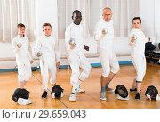 Купить «Group portrait of young fencers with coaches holding rapiers in training room», фото № 29659043, снято 30 мая 2018 г. (c) Яков Филимонов / Фотобанк Лори